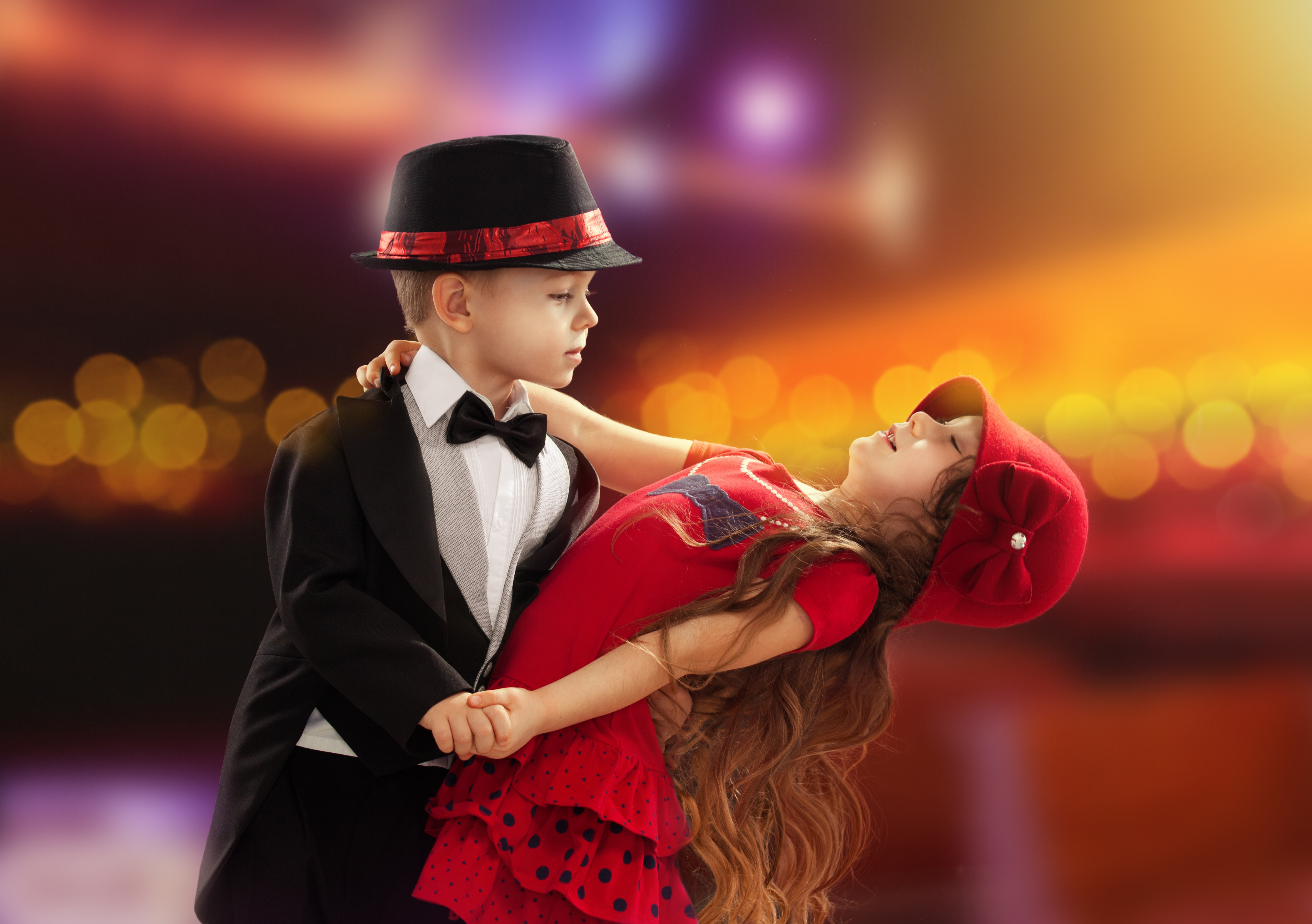 a young boy and girl ballroom dancing in fancy clothing