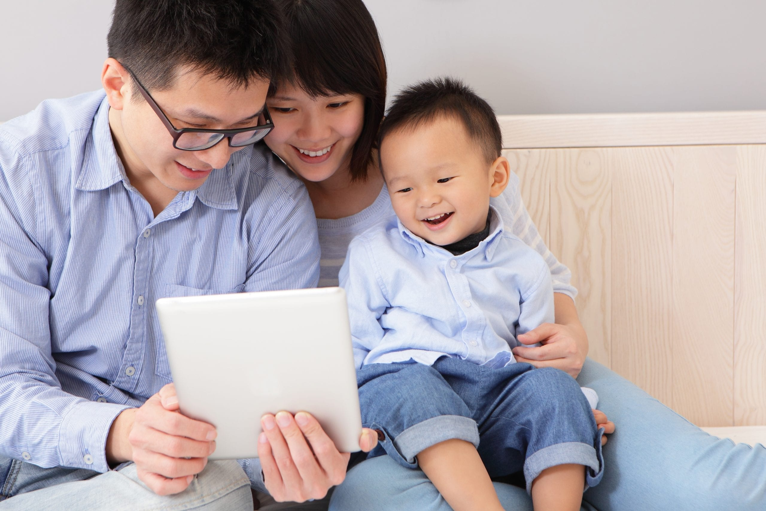 asian couple showing they happy baby an ipad