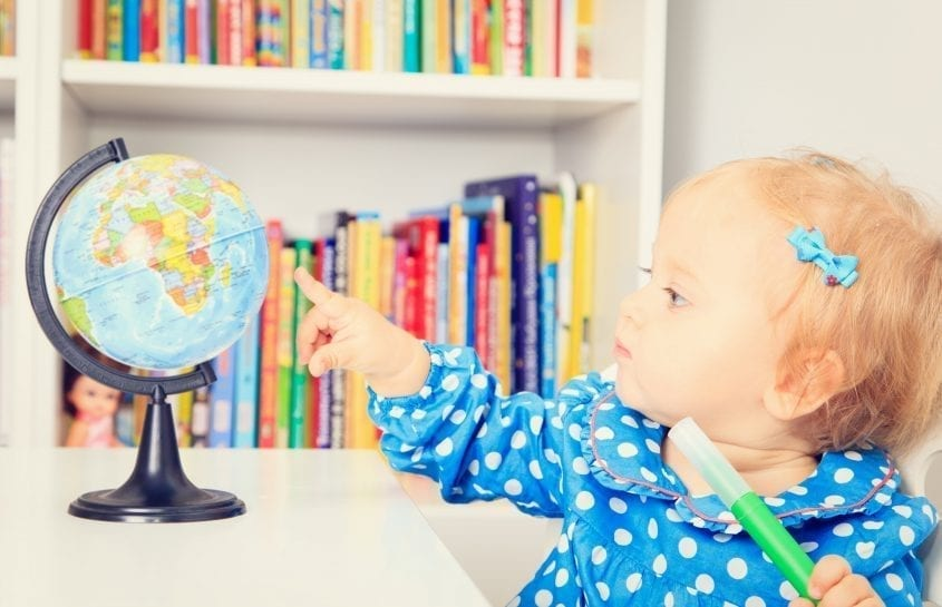 little girl pointing to a globe